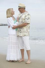 Senior couple stand embracing on beach