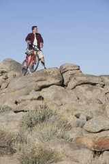 Man stands with mountain bike on rocky outcrop