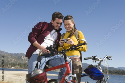 Young couple stand with mountain bike looking at screen of camera