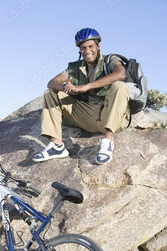Man sits on rock wearing cycling helmet