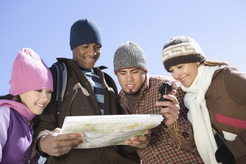 Group of friends stand looking at map together