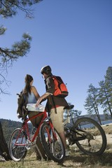 young couple stand with mountain bikes in recreation area