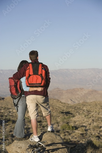Young couple stand looking at view