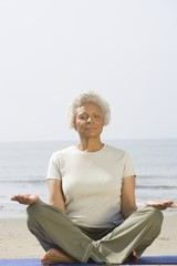 Senior woman sits with legs crossed in yoga pose