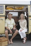Senior couple sit in campervan with pet their dog
