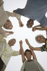Senior friends hold hands and look down at camera