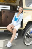 Mature woman sits in open campervan with bicycle