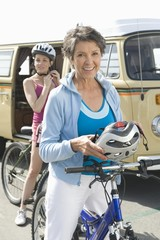 mature and mid adult women prepare for a cycle ride