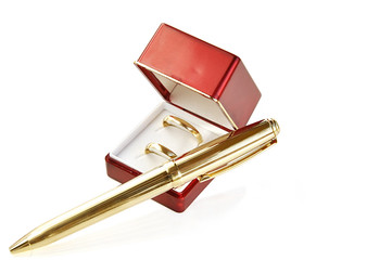 Wedding rings and pen on white with clipping path.