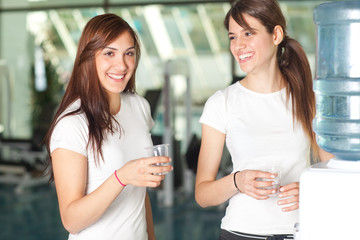 Young women in the gym drinking water