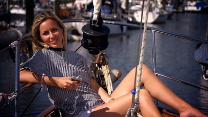 Young girl listening to MP3 player aboard a luxury yacht