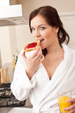 Woman in bathrobe eating toast for breakfast in kitchen poster