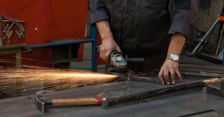 Arbeiterhände in der Metall Industrie mit Trennschleifer
