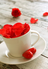 white cup with red petals of roses on old wooden board