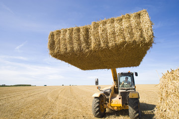 Tractor with straw bale in sunny, rural field