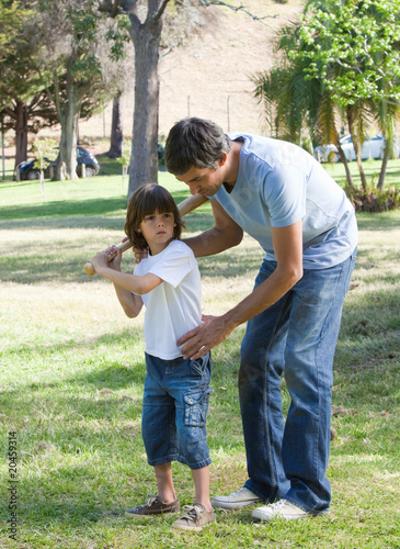 Earing father teaching baseball to his son