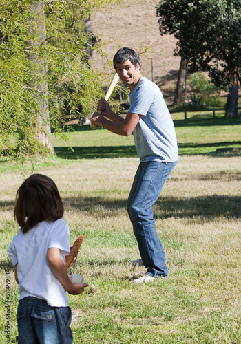 Attractive father playing baseball with his son