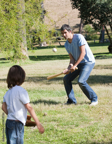 Athletic father playing baseball with his son