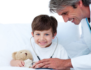 Attentive doctor playing with a little boy