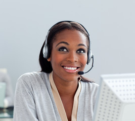 Delighted businesswoman using headset at her desk