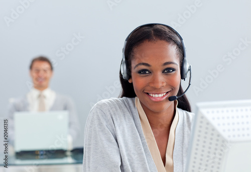 Smiling businesswoman using headset at her desk