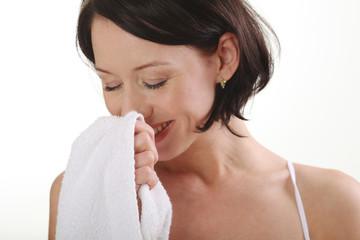 junge Frau riecht an Ihrem Handtuch