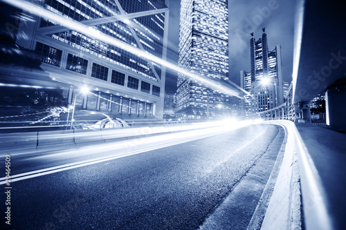 Fast moving cars lights blurred over modern city background - 20464509
