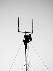 silhouette of worker hanging from antenna and reaching for tool