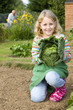 Girl holding cabbage in garden