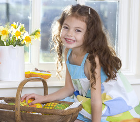 Happy girl with basket of wooden Easter eggs