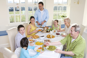 Multi-generation family eating dinner at dining room table