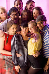 Group of friends at nightclub taking self-portrait with digital camera