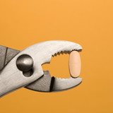 Pill Gripped With Pliers. Isolated poster