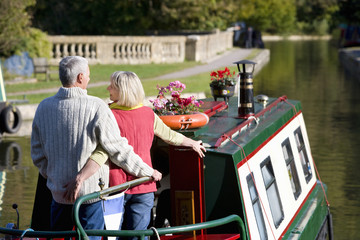 Couple hugging on narrow boat in canal