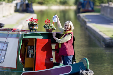 Woman watering potted flowers on boat in canal