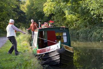 Couple mooring narrow boat in canal