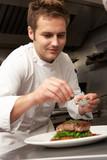 Fototapety Chef Adding Seasoning To Dish In Restaurant Kitchen