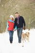 Senior Couple Walking Dog Through Snowy Woodland
