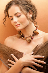 Tanned woman wearing necklace with dried fruits