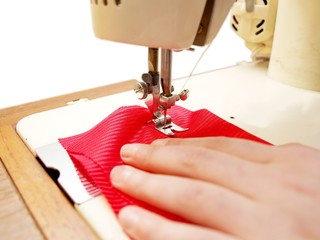 Sewing machine with red clothing on white backgrund
