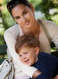Mother and little boy cuddling in park poster
