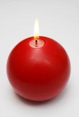 Red round shining candle  on a white background