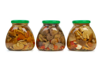 Three glass jars with marinated mushrooms