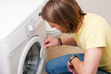 Mann beim Wäsche waschen mit Waschmaschine