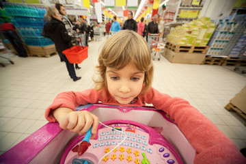 Small girl sit in shoppingcart and examine her new toy