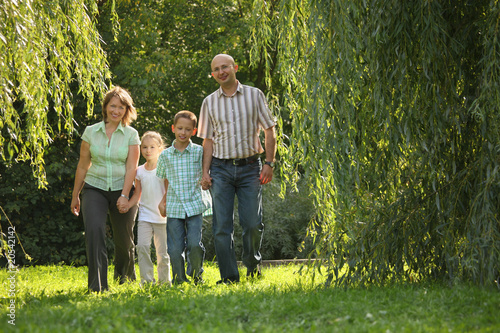 family with two children is walking in early fall park