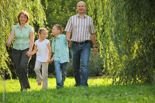 smiling family with two children is walking in early fall park.