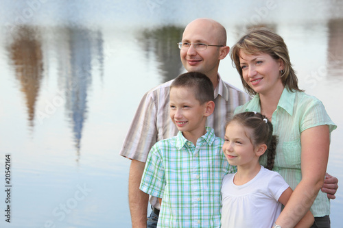 family  on pond background. man is embracing his wife
