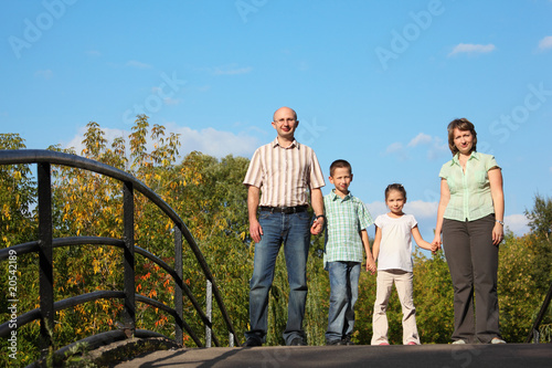 family is standing on bridge and looking at camera.
