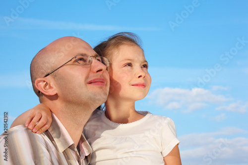 father and little girl on sky background are looking at sky